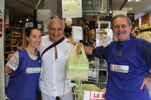 Nduccio consegna un sacchetto della Spesa Sospesa ai volontari del Banco Alimentare